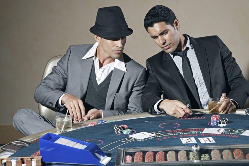 Dois homens jogando poker em uma mesa com fichas e um copo de bebida cada um.
