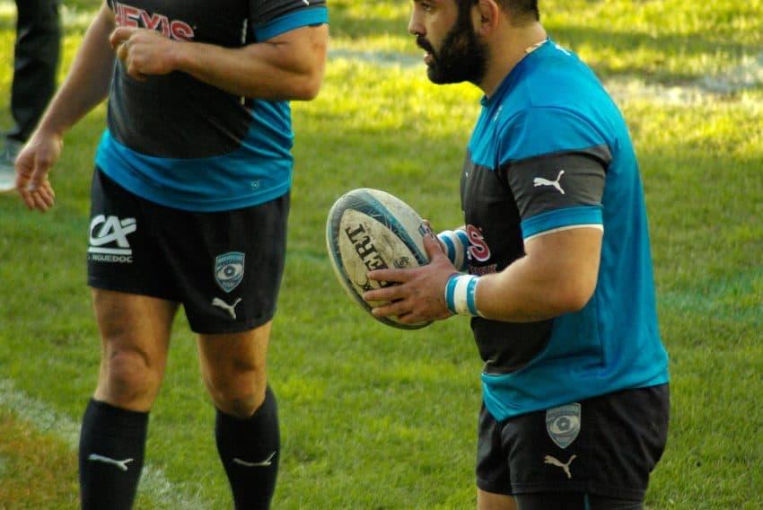 Imagem mostra jogador profissional de rugby segurando uma bola enquanto outro aproxima-se.