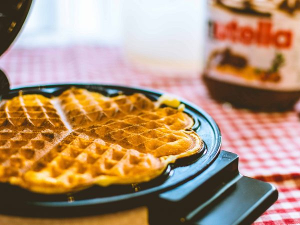 Imagem de máquina de waffle com waffle e pote de creme de avelã ao fundo.