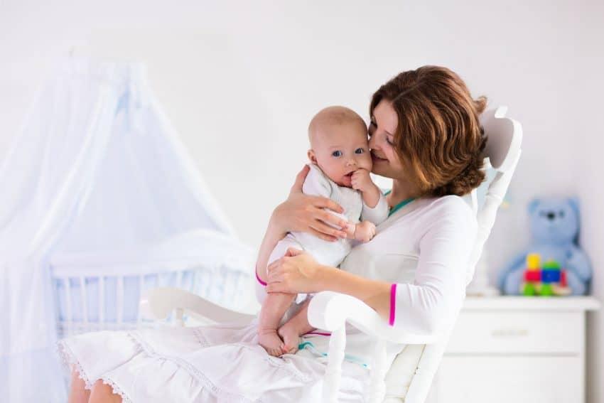 Mãe segurando bebê em poltrona no quarto no bebê.