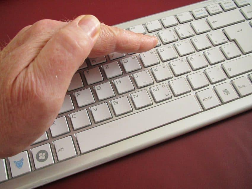 Imagem mostra teclado em cor clara com mão em concha sobre ele na tentativa de reduzir reflexo e melhorar visibilidade.
