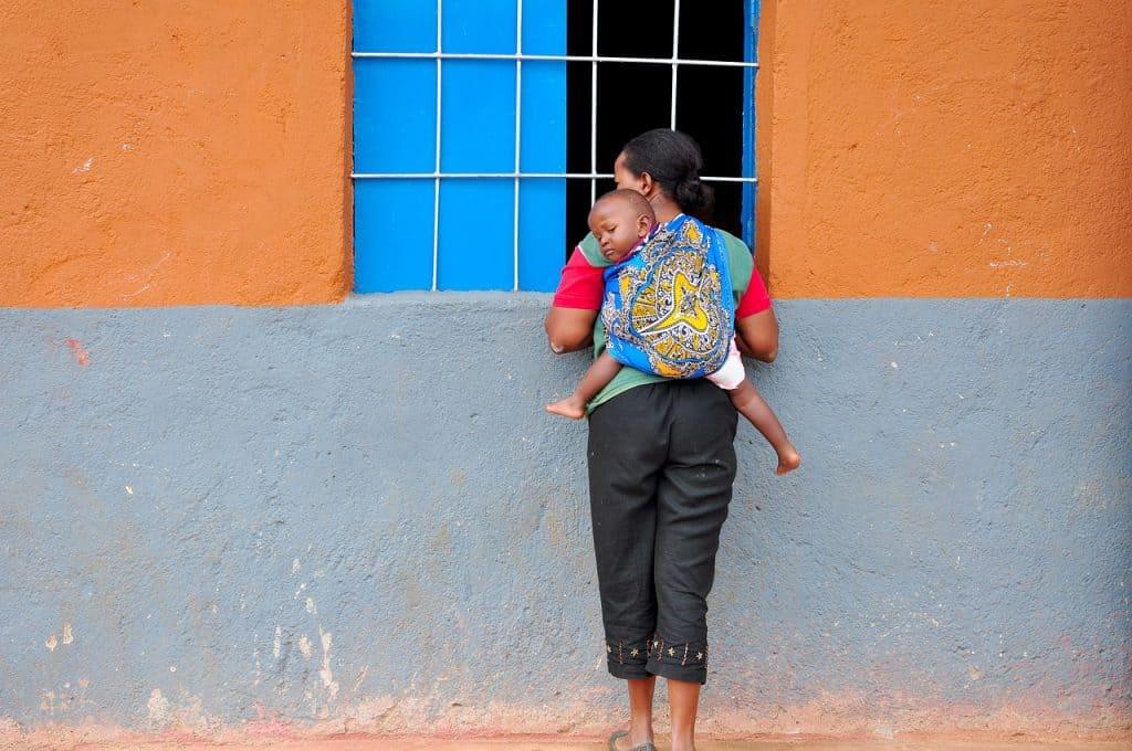 Imagem mostra uma mulher de pé, em frente a uma janela, e uma criança amarrada às suas costas com o auxílio de um sling.