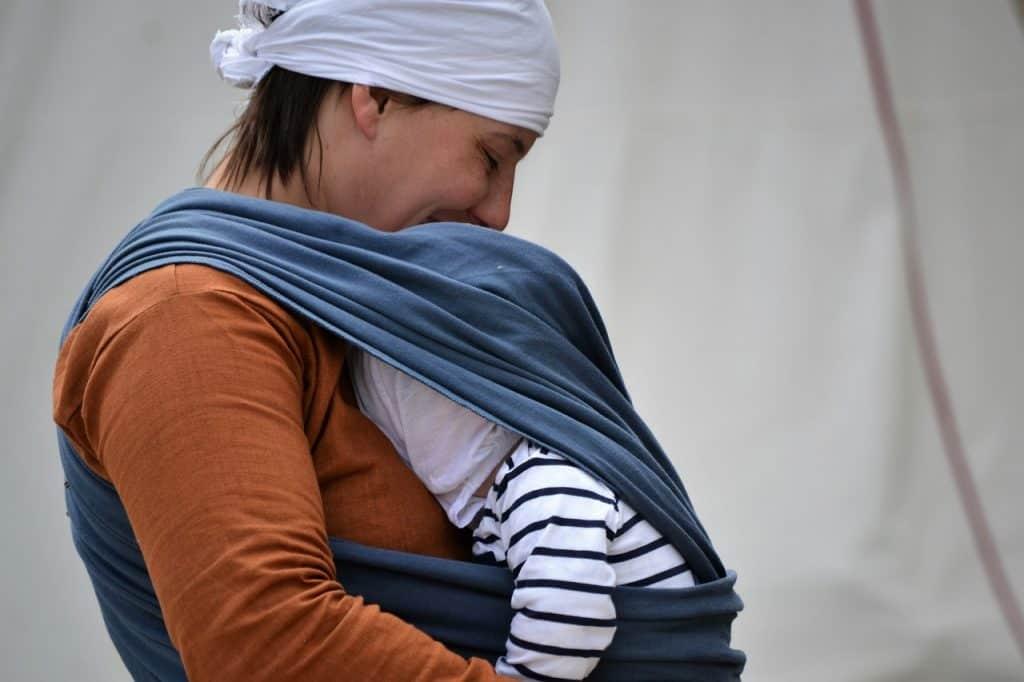 Imagem mostra uma mulher carregando o bebê junto ao corpo em um sling de pano.