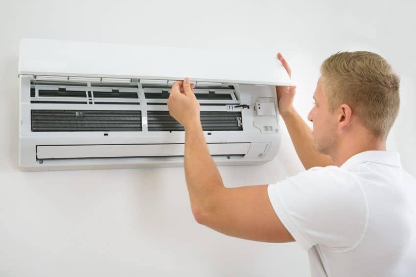 Foto de um homem de camiseta branca, ajustando um ar condicionado de parede.