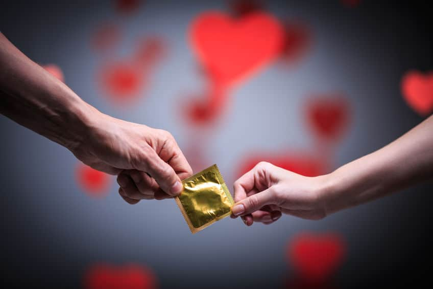 duas mãos segurando uma preservativo fechado