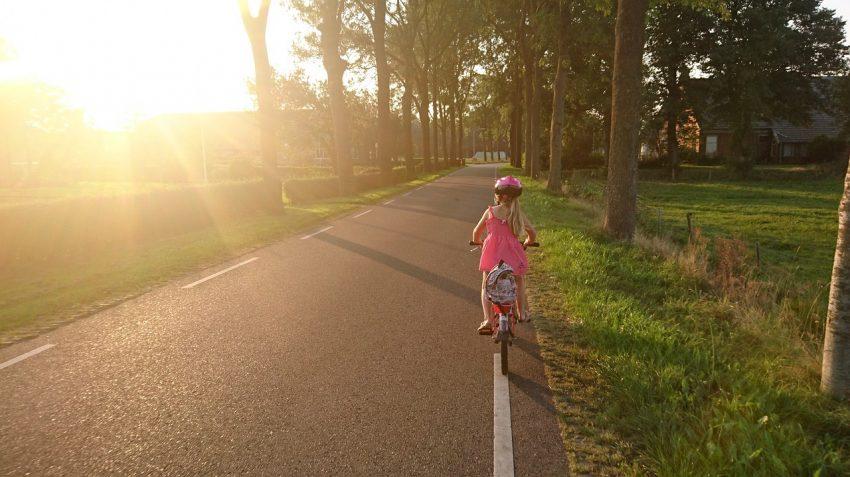 Imagem mostra uma menina pedalando em uma rua e usando capacete.