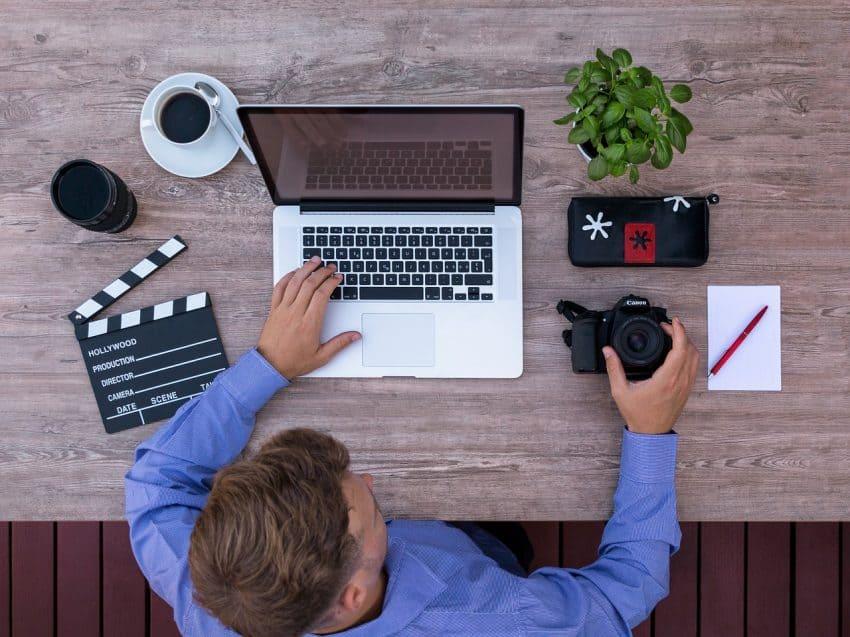 Homem em uma mesa de trabalho com um notebook.
