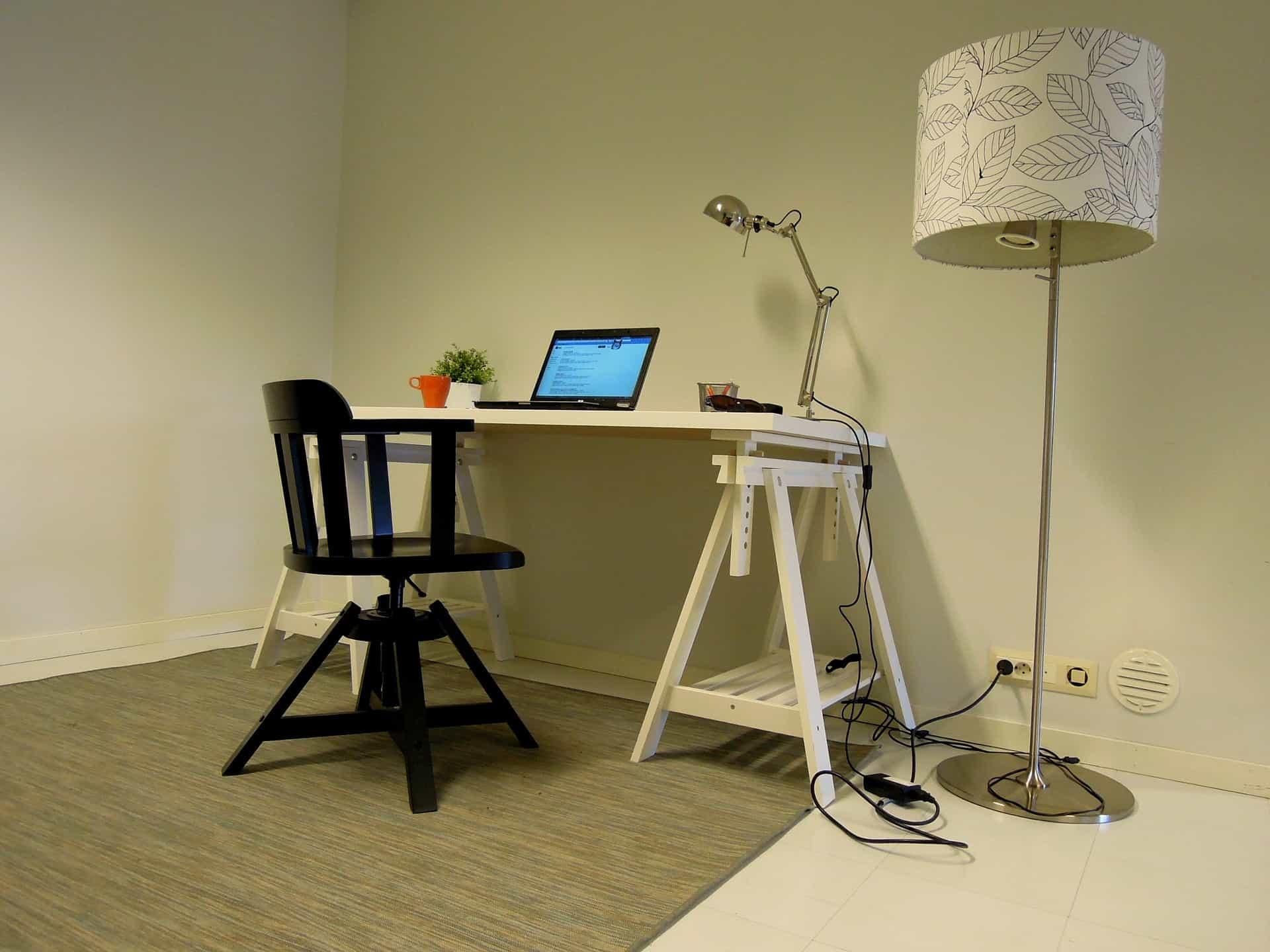 Mesa com com notebook em cima, cadeira vazia.