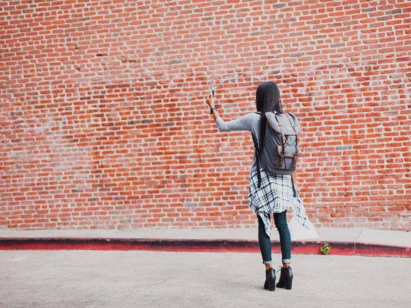 Menina passeando e fazendo selfie com mochila nas costas.