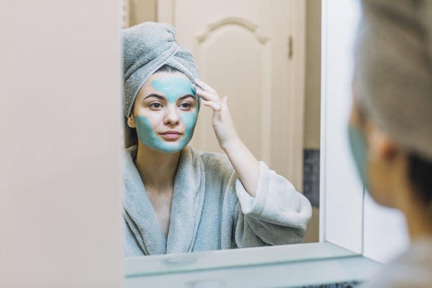 Moça aplica máscara facial enquanto usa roupão de banho e toalha nos cabelos.