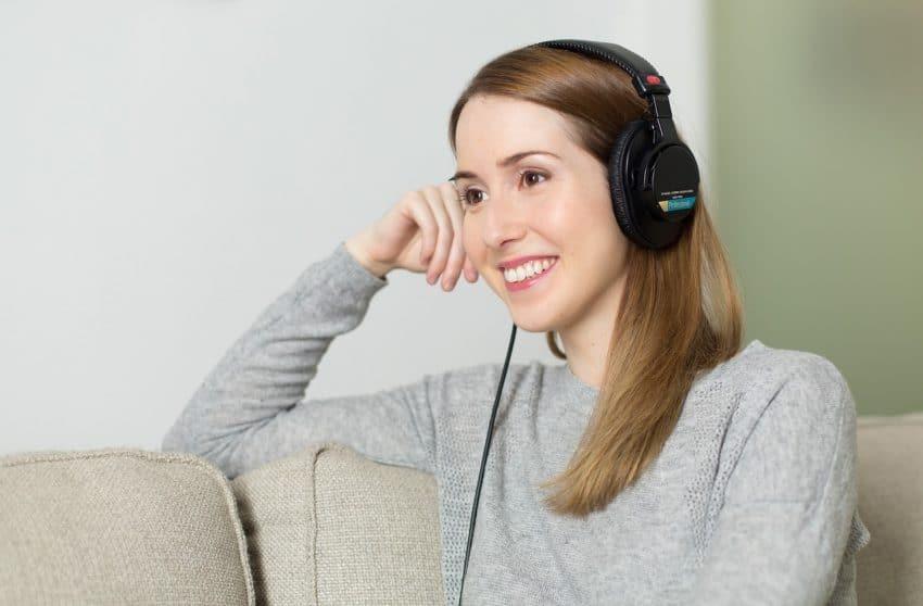 Mulher com fone de ouvido grande com alças, sentada no sofá.