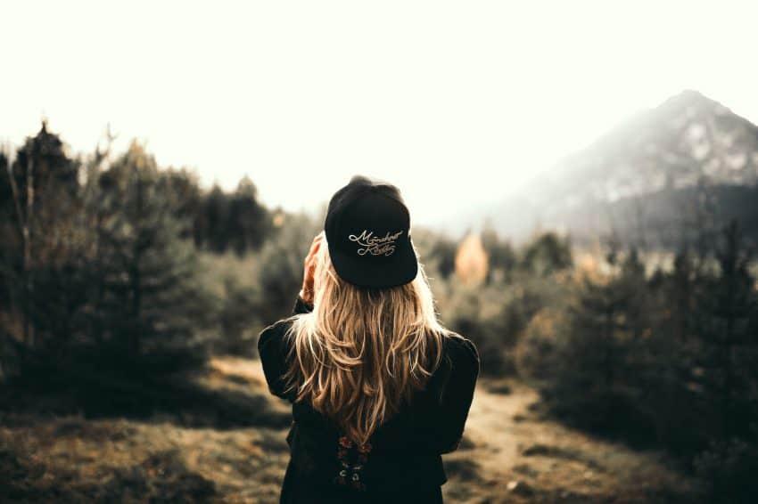 Imagem mostra uma mulher de costas, com um aba reta preto virado para trás, sob longos cabelos loiros. Ao fundo, uma floresta de pinheiros desfocado.