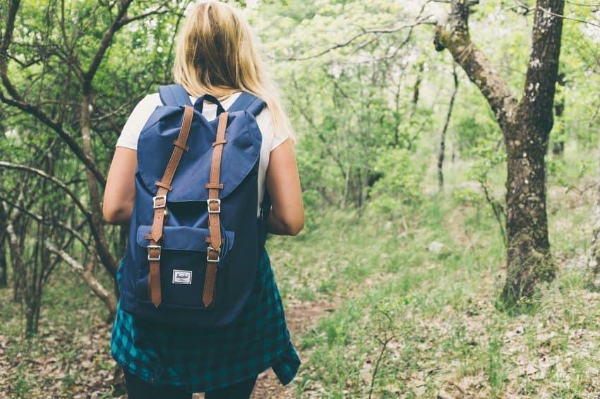 Menina andando na mata com mochila azul nas costas.