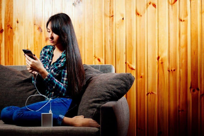 Mulher usando celular no sofá.