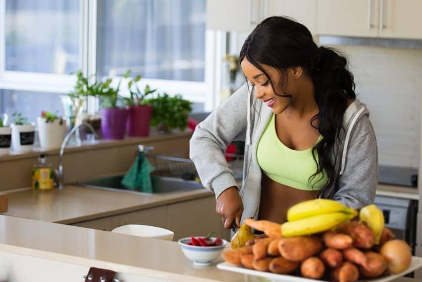 Na imagem uma mulher com roupa de ginástica dentro de uma cozinha cortando uma pera.