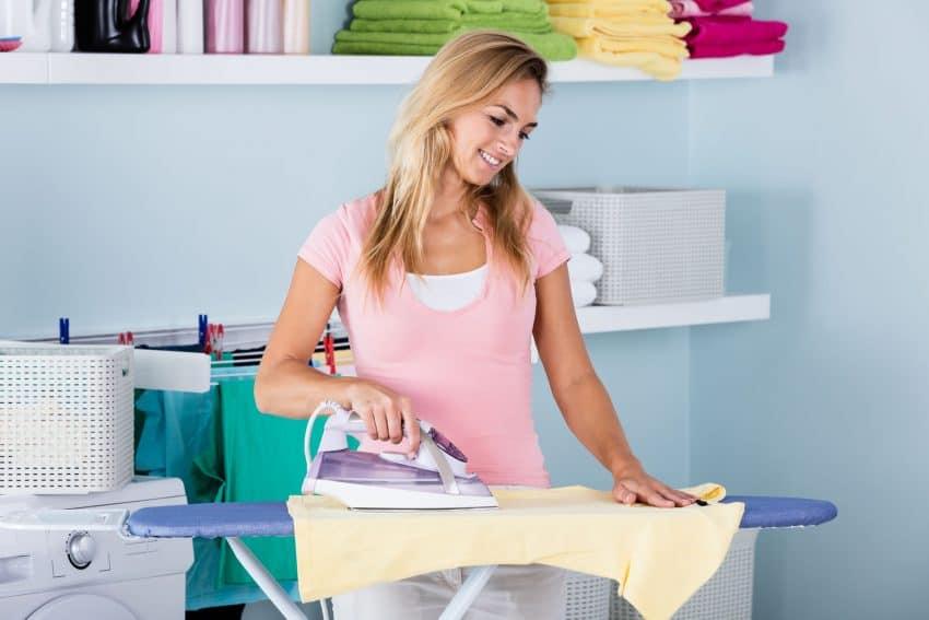Mulher passando roupa na área de serviço com tábua de passar.
