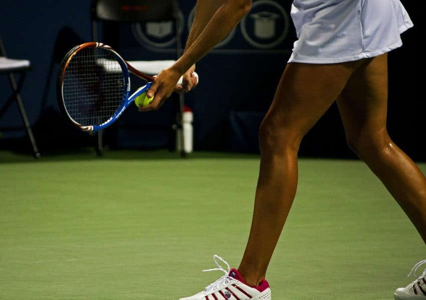 Mulher sacando com uma bola e raquete de tênis na mão.