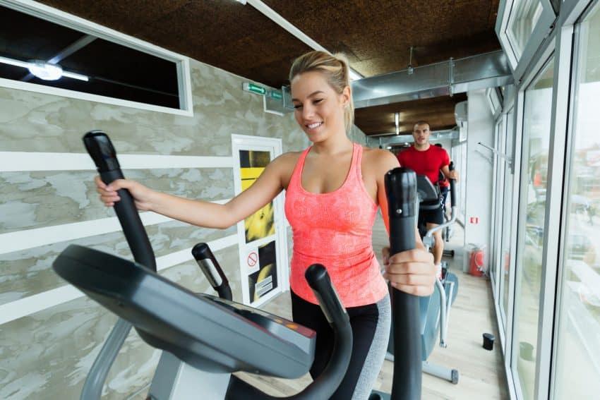 Mulher se exercitando com um simulador de caminhada.