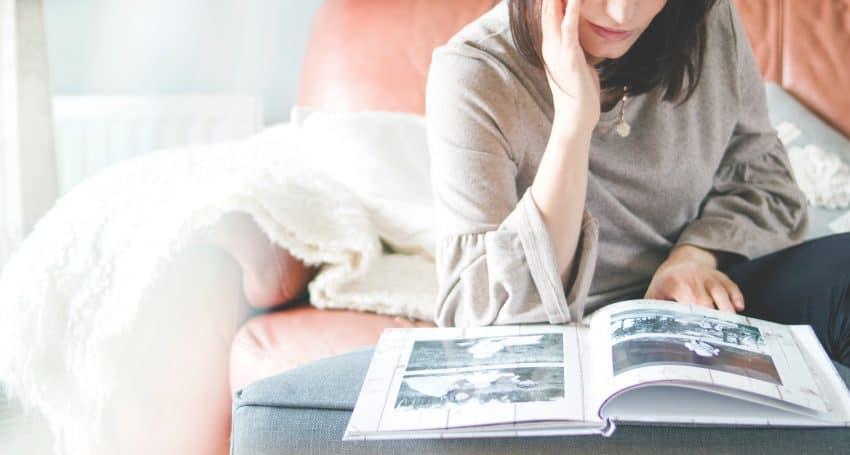 Foto de uma mulher sentada em um sofá, olhando um álbum de fotos.