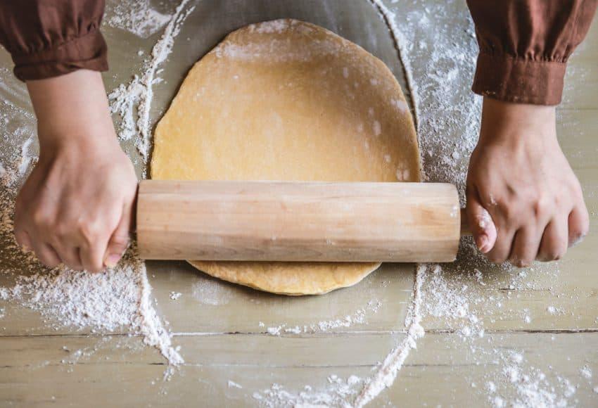 Foto tirada de cima, de um padeiro preparando uma massa de pão.