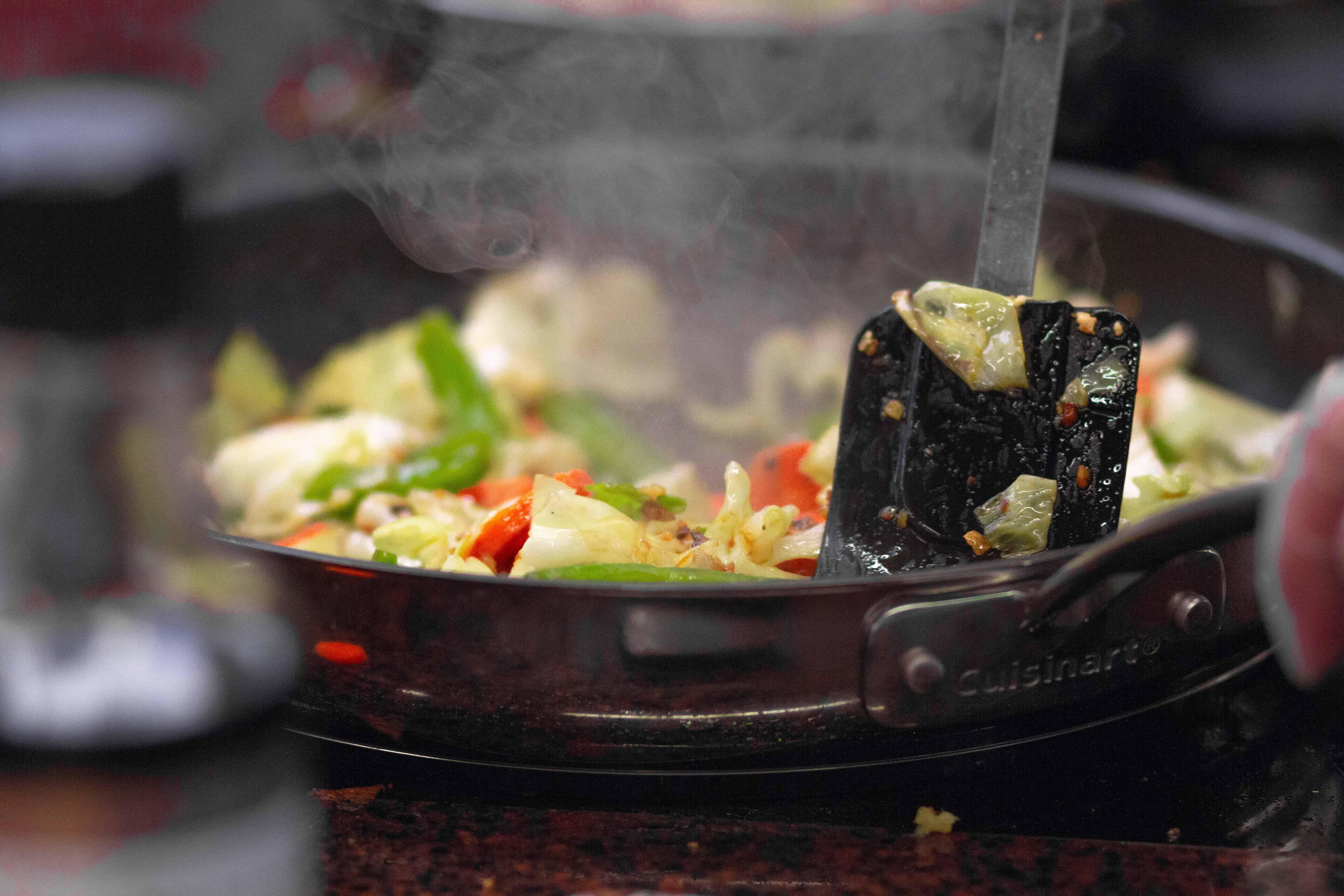 Foto de uma panela de ferro preta, com comida sendo preparada em seu interior, em uma colher preta.