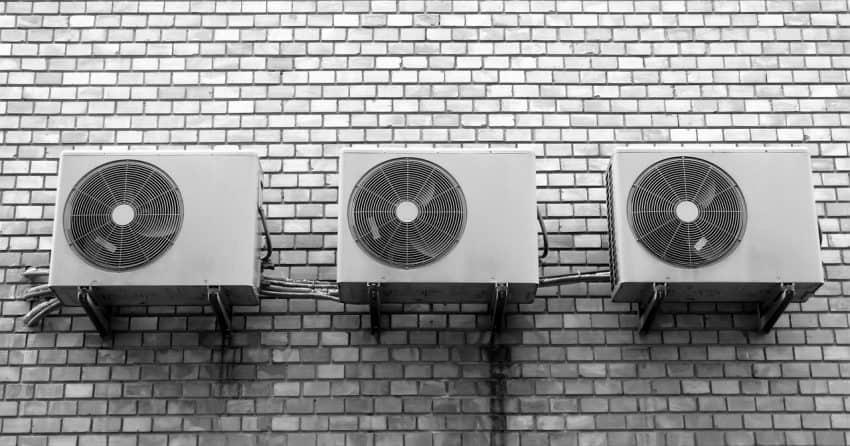 Foto em preto e branco da parte externa de três ar condicionados, presos a uma parede de pequenos tijolos.