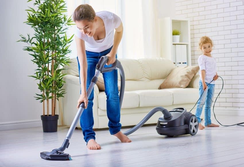 Mulher aspirando o chão da sala e filha ajudando na limpeza.