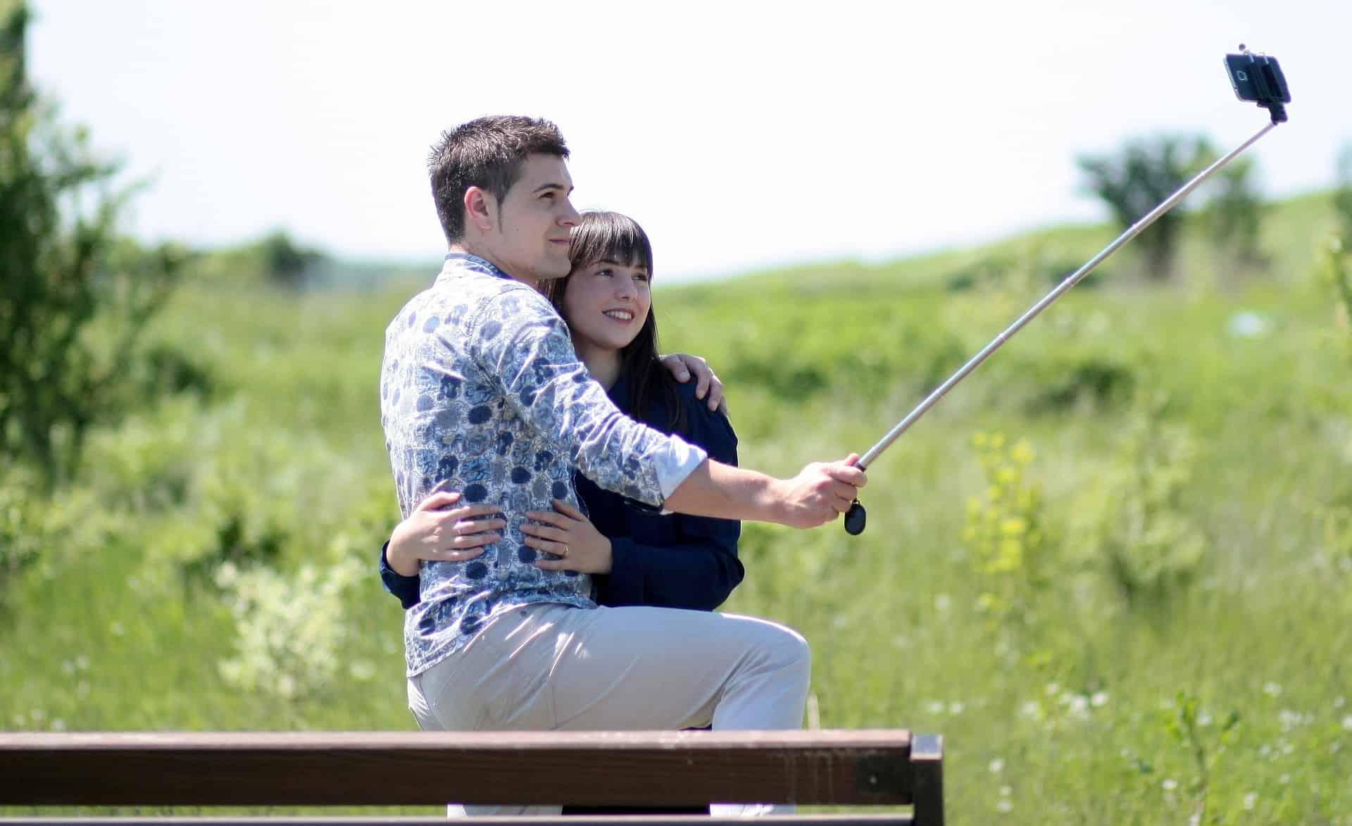 Imagem de um casal abraçado, tirando foto com um pau de selfie, em um espaço aberto, com um fundo de natureza.