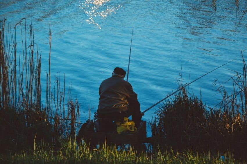 Homem pescando sentado à beira de um lago ao anoitecer.