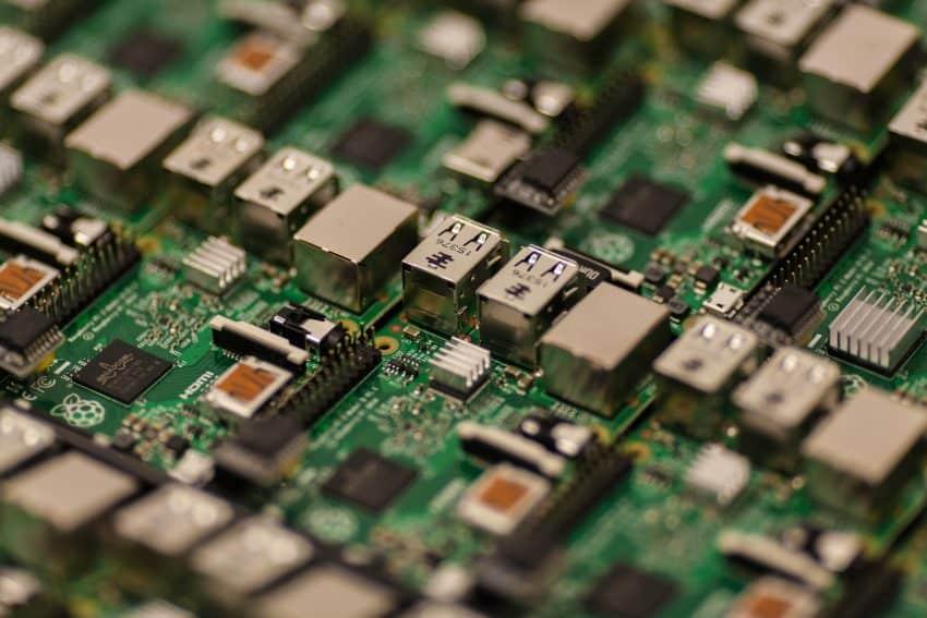Imagem mostra uma placa de rede, com vários circuitos prateados alinhados e focados.