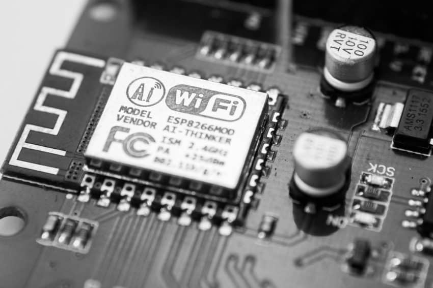 Imagem mostra uma placa de rede pequena, com foco no símbolo de WiFi sob um dos circuitos.