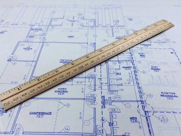 Imagem de régua de madeira sobre plano de planta baixa.