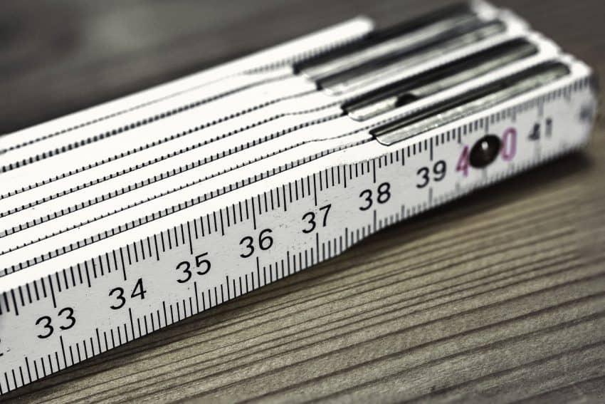 Imagem de régua dobrável branca de madeira com medição em centímetros e milímetros sobre bancada de madeira.