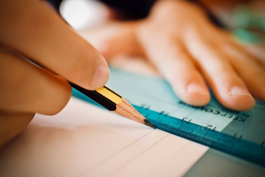 Imagem de pessoa utilizando uma régua de plástico azul com um lápis preto e vermelho para traçar uma linha em uma folha de papel branco.
