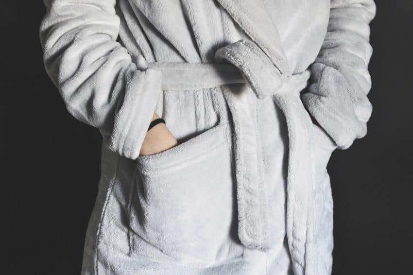 Imagem mostra tronco de uma pessoa com as mãos no bolso de um roupão.