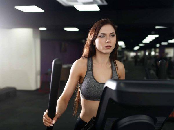 Mulher se exercitando na academia em um simulador de caminhada.