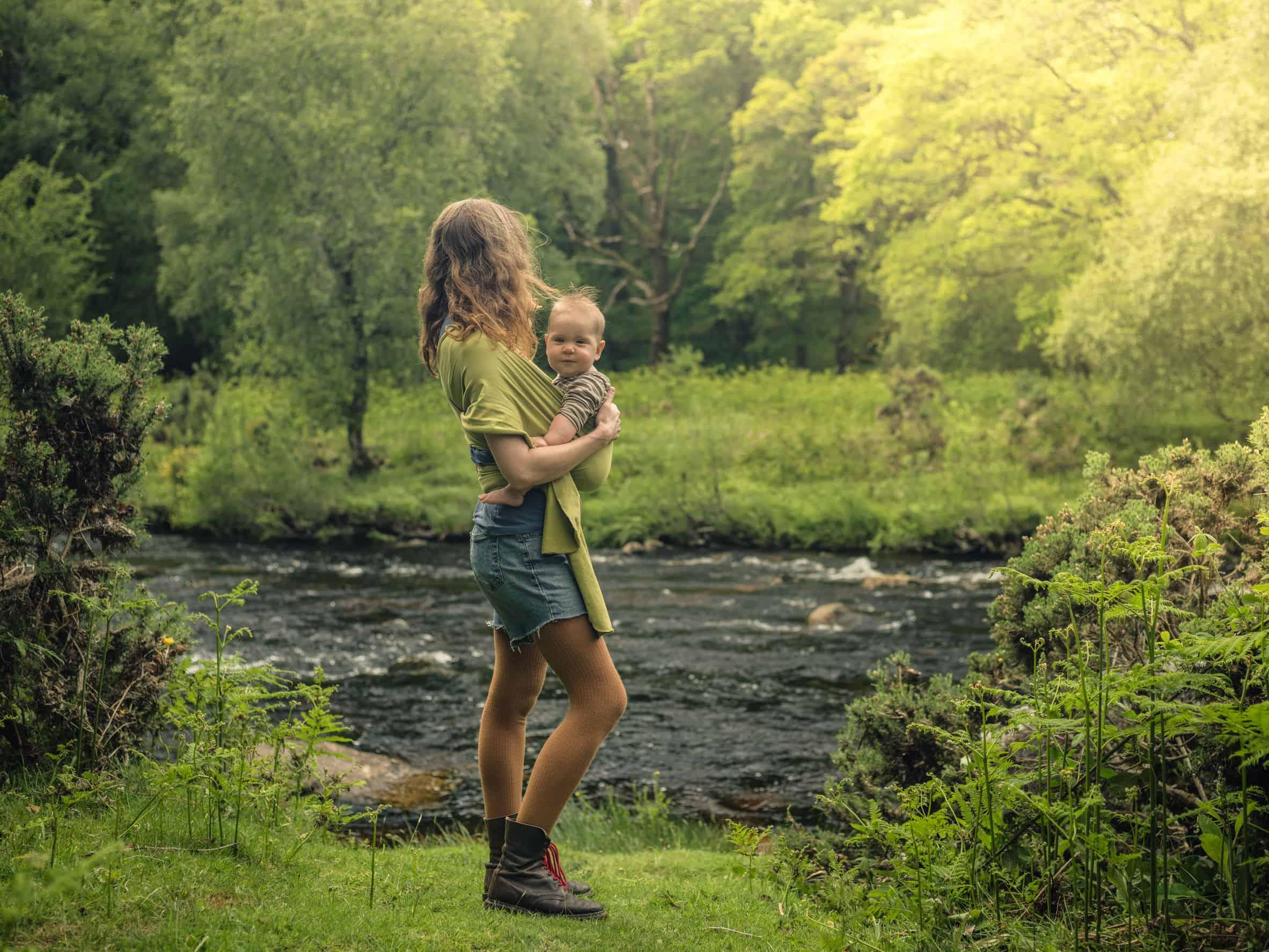 jovem mãe com seu filho em um sling em meio à natureza