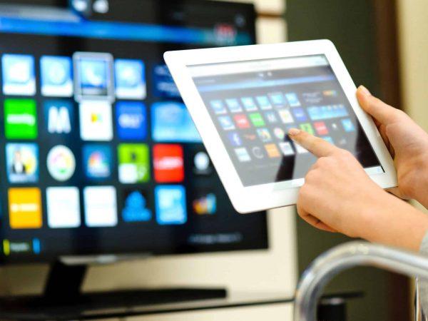 Pessoa controlando smart tv através de um tablet.