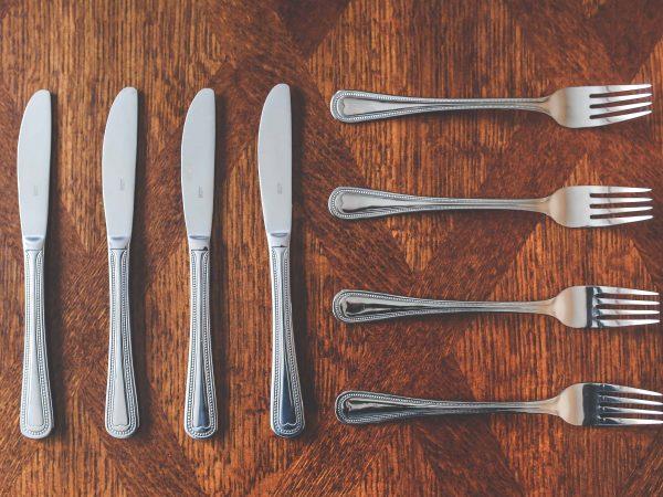 Na foto há quatro facas e quatro garfos sobre uma mesa de madeira escura.