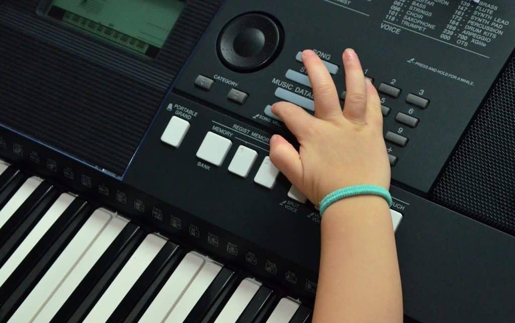 Foco no teclado com uma mão infantil apertando uma tecla.