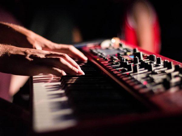 Duas mãos tocando um teclado musical em um fundo escuro.