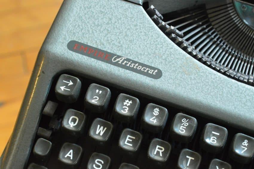 Foto de antiga máquina de escrever com foco nas teclas da primeira fileira que formam o termo QWERTY.