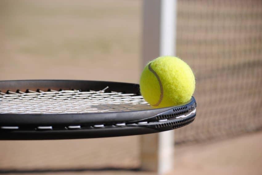 bola de tênis posicionada sobre uma raquete na horizontal com quadra de tênis desfocada em segundo plano