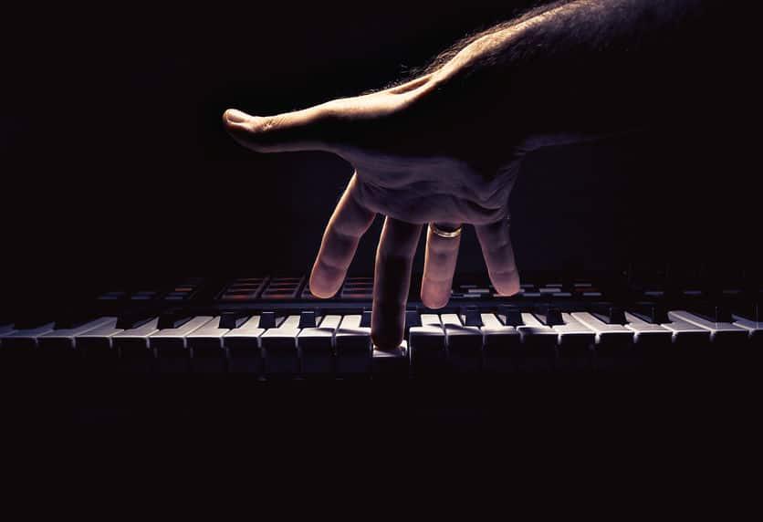 mão tocando teclado musical