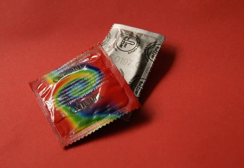 Imagem de pacotes de camisinha sob fundo vermelho.