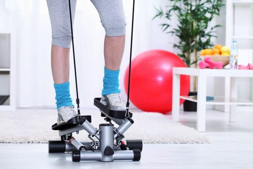 Imagem mostra pernas de uma mulher usando simulador de caminhada em casa.