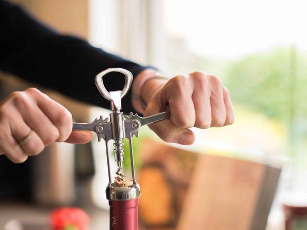 Imagem com foco nas mãos de uma pessoa que usa um abridor de vinhos para abrir uma garrafa de vinho.