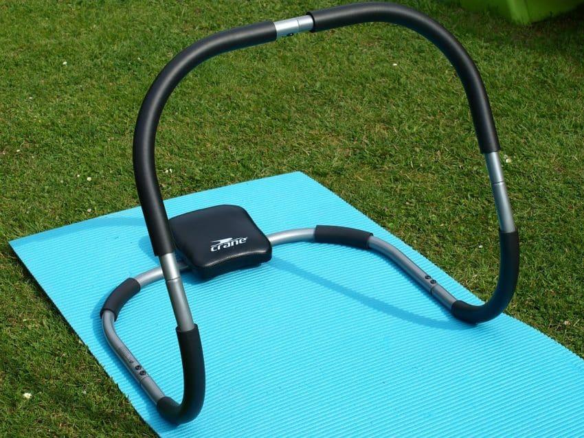 Aparelho abdominal na grama com um tapete de cor azul por baixo.