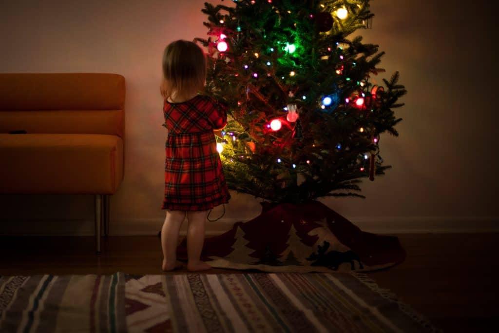 Imagem de uma menina perto de uma árvore de natal