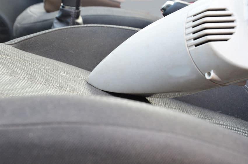 Aspirador de pó automotivo branco sendo passado no carro.